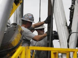 Crew members with Anadarko Petroleum Corp. work on a drilling platform in 2009 on a Weld County farm near Mead, Colo. AP File Photo