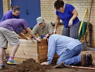 Standing at right is Principal Ruthie Rayner. Kneeling is Bob Eichenberg. Behind the box with ball cap is Jerry Newhouse, with the Oklahoma Organic Gardening Association. Volunteers are planting a garden at Stanley Hupfeld Academy at Western Village. Photo by Jim Beckel, The Oklahoman. Jim Beckel