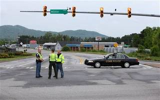 Cobb County Police block off Old US 41 Highway after an early morning workplace shooting at the Airport Road FedEx facility Tuesday April 29, 2014, in Kennesaw, Ga. A shooter opened fire at a FedEx center wounding at least six people before police swarmed the facility. The shooter was found dead from an apparent self-inflicted gunshot wound. (AP Photo/Jason Getz)
