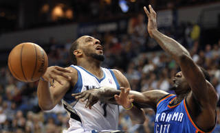 Oklahoma City Thunder's Kendrick Perkins, right, bats the ball away from Minnesota Timberwolves' Derrick Williams as Williams attempts to go to the basket during the first quarter of an NBA basketball game, Saturday, April 14, 2012, in Minneapolis. (AP Photo/Tom Olmscheid) ORG XMIT: MNTO101