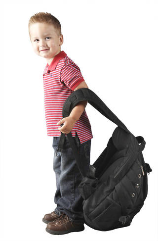 Avery Garrison-Rice, 3, is overwhelmed by a large backpack. Photo by Doug Hoke, The Oklahoman
