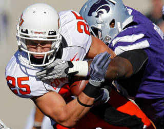 Oklahoma State's Josh Cooper (25) is hit by after a reception by a member of the Kansas State defense during the first half of the college football game between the Oklahoma State University Cowboys (OSU) and the Kansas State University Wildcats (KSU) on Saturday, Oct. 30, 2010, in Manhattan, Kan. Photo by Chris Landsberger, The Oklahoman