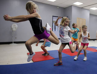 Ella Hodges, 7, practices leaps with other participants at a cheer and tumbling camp this week sponsored by Norman's Parks and Recreation Department. PHOTOs BY STEVE SISNEY, THE OKLAHOMAN