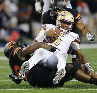 Florida State's Jameis Winston, center, is sacked by OSU's Emmanuel Ogbah, bottom, during Saturday's season opener in Arlington, Texas. Photo by Chris Landsberger, The Oklahoman