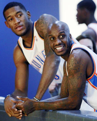 Oklahoma City Thunder's Perry Jones, left, and Walker Russell, right, watch their teammates during NBA basketball media day in Oklahoma City, Monday, Oct. 1, 2012. (AP Photo/Sue Ogrocki)
