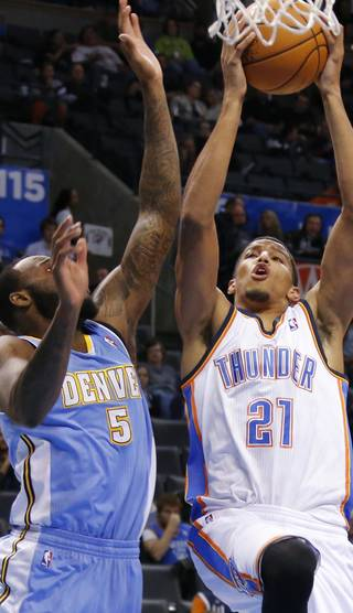 OKC's Andre Roberson, right, looks to score while being defended by Denver's Damion James during a game earlier this season. Photo by Bryan Terry, The Oklahoman
