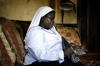 Sister Rosemary Nyirumbe sews a strap onto a pop-tab purse Tuesday at the home of Reggie and Rachelle Whitten of Oklahoma City. SARAH PHIPPS - SARAH PHIPPS