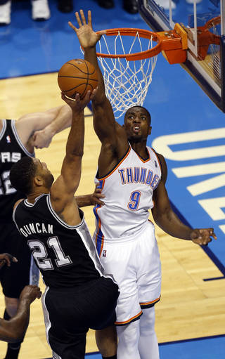 Oklahoma City's Serge Ibaka (9) blocks the shot of San Antonio's Tim Duncan (21) during Game 3 of the Western Conference Finals in the NBA playoffs between the Oklahoma City Thunder and the San Antonio Spurs at Chesapeake Energy Arena in Oklahoma City, Sunday, May 25, 2014. Photo by Nate Billings, The Oklahoman