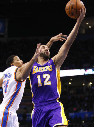 Los Angeles Lakers guard Kendall Marshall (12) goes to the basket in front of Oklahoma City Thunder guard Andre Roberson (21) during the first quarter of an NBA basketball game in Oklahoma City, Thursday, March 13, 2014. (AP Photo/Alonzo Adams)