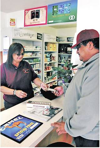 Susan Isham, a clerk at the Wetumka Indian Community Smokeshop, sells cigarettes to Chris Powell. Customers pay about $1 dollar less for a pack of cigarettes, partly because the tribe pays less in taxes, manager Phyllis Noon said.