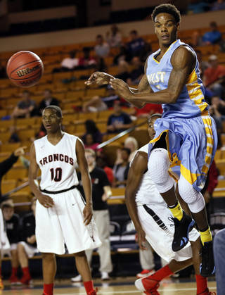 Putnam City West's Omega Harris, right, passes the ball during the Patriots' Class 6A state semifinal victory over Mustang.