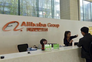 A receptionist talks to a visitor Wednesday at the headquarters campus of Alibaba Group in Hangzhou in China's Zhejiang province. AP Photo - AP