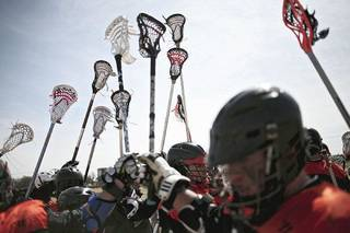 OSU's lacrosse team members hold up their sticks after getting instructions during a timeout Sunday. PHOTO BY JOHN CLANTON, THE OKLAHOMAN John Clanton