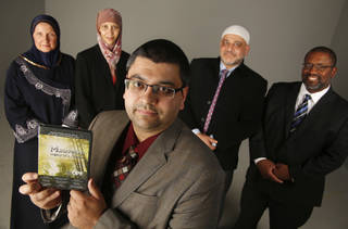 Adam Soltani, foreground, with the Council on American-Islamic Relations Oklahoma Chapter, shows a copy of a free DVD his organization is giving away to non-Muslims interested in learning about the life of the Prophet Muhammad. Others pictured are, from left, Sheryl Siddiqui, Jenell Mapp-Maynard, Imad Enchassi and Saad Mohammed. Photo by Doug Hoke, The Oklahoman