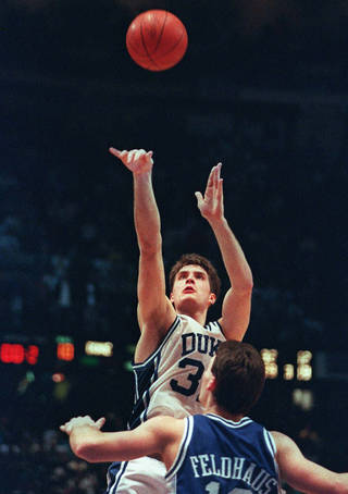 FILE - In this March 28, 1992 file photo, Duke's Christian Laettner shoots the game-winning basket in overtime over Kentucky's Deron Feldhaus to win the NCAA East Finals in Philadelphia March 28, 1992. Laettner's big shot in 1992 is among the memorable moments in NCAA tournament history. (AP Photo/Charles Arbogast, File) ORG XMIT: NY155