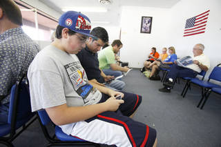 Carter Cortez, 15yr plays a vedio game and waits with his father John Cortez at the Oklahoma Department of Motor Vehicles in Yukon, Thursday 19, 2012. Photo By Steve Gooch, Cortez was waiting to get his drivers permit. The Oklahoman