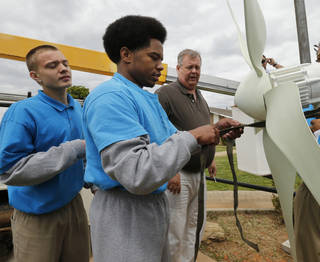 DeVonte Matlock, 18, front right, and Dyllan Hulsey, 17, left, prepare to install a wind turbine at the Central Oklahoma Juvenile Center on Wednesday in Tecumseh . Teens from the center have worked on wind turbine components and they are installing their turbine. Roger Farris, Gordon Cooper Technology Center director of instruction is behind them. Photo by Steve Sisney, The Oklahoman STEVE SISNEY - THE OKLAHOMAN