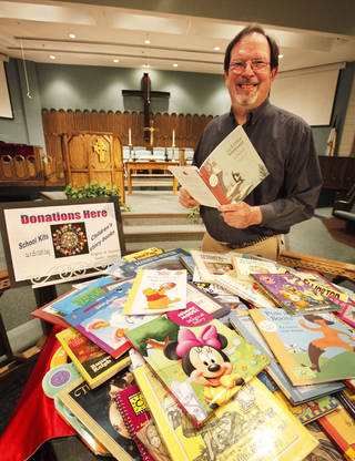 Rev. Ed Light of Grace United Methodist Church in Oklahoma City shows some of the books collected to give Tulsa inmates to read to their children on tape. Photo By David McDaniel, The Oklahoman