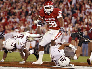 Oklahoma's Chris Brown (29) makes his way into the endzone past Texas A&M's Jordan Pugh (25) and Trent Hunter (1) during the second half of the college football game between the University of Oklahoma Sooners (OU) and the Texas A&M Aggies at Gaylord Family-Memorial Stadium on Saturday, Nov. 14, 2009, in Norman, Okla. Photo by Chris Landsberger, The Oklahoman