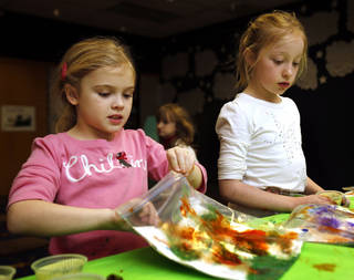 Greta Mansell, 7, and Lydia Stuart, 8, make paintings inside plastic bags during the after-school special story time at the Norman Public Library. PHOTO BY STEVE SISNEY, THE OKLAHOMAN STEVE SISNEY