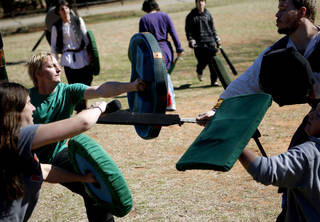 Shaun Anderson, left, fights as he practices Dagorhir battle games at E.C. Hafer Park. A group of Dagorhir players meet on Saturdays in the park. PHOTO BY BRYAN TERRY, THE OKLAHOMAN. BRYN TERRY - THE OKLAHOMAN