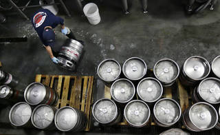 Brewer Ken Hermann rolls a fresh keg of beer onto pallets at the Harpoon Brewery in the Seaport District of Boston. AP File Photo Charles Krupa