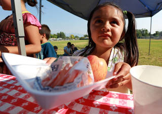 Jasmine Alfaro gets dinner outside of the Central Park Community Center in South Salt Lake on Friday, July 18, 2014. The dinner is part of the Salt Lake CAP summer food program, which offers free dinner to children at five locations in the valley, Monday through Friday.