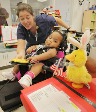 21 month old Taliya McDaniel and her Occupational Therapy Assistant Rachel George guide a n electronic duck over the finish line at the Children's Center in Oklahoma City, Thursday August 9, 2012. The center is holding Olympic games for the children at the center. Photo By Steve Gooch, The Oklahoman Steve Gooch - The Oklahoman