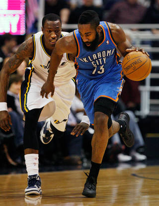 Oklahoma City Thunder guard James Harden, right, takes control of a loose ball against Utah Jazz forward Josh Howard, left, during the first half of their NBA basketball game in Salt Lake City, Friday, Feb. 10, 2012. (AP Photo/Steve C. Wilson) ORG XMIT: UTSW106
