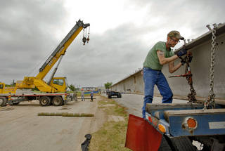 INTERSTATE 40 / CROSSTOWN EXPRESSWAY / HIGHWAY / BEAMS: David Rhoads works to unload two 20,000-pound steel beams that were the first to be removed from the I-40 crosstown bridge on Monday, May 7, 2012, in Edmond, Oklahoma. The two 90-foot beams will be part of the Deer Creek flood control bridge project on MacArthur near Covell. There will be a total of 1,914 beams removed from I-40 to be repurposed in bridge projects across the state. Photo by Chris Landsberger, The Oklahoman