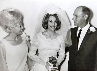 Shonsy Sybert is pictured on her wedding day with her parents, Laura and Harold Trumbly. Sybert's sister also wore the dress on her own wedding day. Photo provided. provided - The Oklahoman