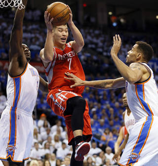 Houston's Jeremy Lin (7) passes away from Oklahoma City's Kendrick Perkins (5) and Thabo Sefolosha (2) during Game 2 in the first round of the NBA playoffs between the Oklahoma City Thunder and the Houston Rockets at Chesapeake Energy Arena in Oklahoma City, Wednesday, April 24, 2013. Photo by Nate Billings, The Oklahoman