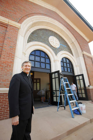 The Rev. Joseph Jacobi stands near the entrance to the new church building under construction at St. Eugene Catholic Church, 2400 W Hefner Road in The Village. PAUL B. SOUTHERLAND - PAUL B. SOUTHERLAND