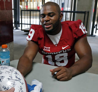 Linebacker Eric Striker signs autographs during the University of Oklahoma (OU) football team's annual Meet the Sooners day at Gaylord Family/Oklahoma Memorial Stadium Saturday, Aug. 2, 2014 in Norman, Okla. Photo by Steve Sisney, The Oklahoman