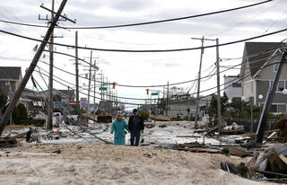 Robert Bryce, right, walkswith his wife, Marcia Bryce, through destruction from superstorm Sandy on Route 35 in Seaside Heights, N.J., Wednesday, Oct. 31, 2012. Sandy, the storm that made landfall Monday, caused multiple fatalities, halted mass transit and cut power to more than 6 million homes and businesses. (AP Photo/Julio Cortez) ORG XMIT: NJJC109