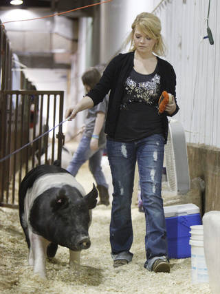 "Yukon senior Kaylen Baker guides ""Grandp"" down an aisle between stalls March 15 at the Oklahoma Youth Expo. PAUL HELLSTERN - Oklahoman"