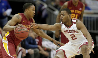 Oklahoma guard Steven Pledger (2) tires to steal the ball from Iowa State guard Tyrus McGee during the first half an NCAA college basketball game in the Big 12 Conference tournament Thursday, March 14, 2013, in Kansas City, Mo. (AP Photo/Charlie Riedel) ORG XMIT: MOCR103