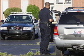 A Warr Acres police officer interviews a driver Tuesday after a Putnam City School District student was struck at NW 42 and Grove Avenue in Warr Acres. Photo by Paul B. Southerland, The Oklahoman PAUL B. SOUTHERLAND - PAUL B. SOUTHERLAND