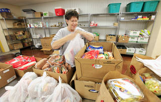 Volunteer Phyllis Purcer bags food for clients to pick up at BritVil Community Food Pantry. PHOTO BY PAUL B. SOUTHERLAND, THE OKLAHOMAN PAUL B. SOUTHERLAND - PAUL B. SOUTHERLAND