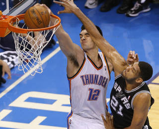 Oklahoma City's Steven Adams (12) dunks beside San Antonio's Tim Duncan (21) during Game 4 of the Western Conference Finals in the NBA playoffs between the Oklahoma City Thunder and the San Antonio Spurs at Chesapeake Energy Arena in Oklahoma City, Tuesday, May 27, 2014. Photo by Bryan Terry, The Oklahoman