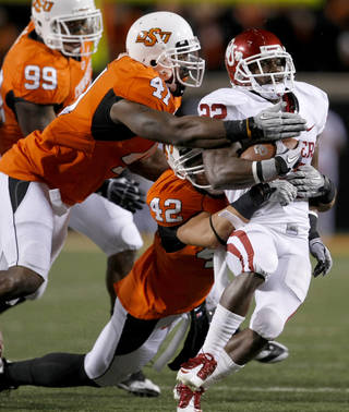 Oklahoma's Roy Finch (22) is brought down by Oklahoma State's Orie Lemon (41) and Oklahoma State's Justin Gent (42) during the Bedlam college football game between the University of Oklahoma Sooners (OU) and the Oklahoma State University Cowboys (OSU) at Boone Pickens Stadium in Stillwater, Okla., Saturday, Nov. 27, 2010. Photo by Bryan Terry, The Oklahoman