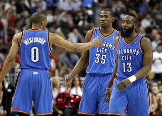 Oklahoma City Thunder's Russell Westbrook, left, reacts with teammates Kevin Durant (35) and James Harden (13) near the end of the first half of an NBA basketball game with the Philadelphia 76ers, Wednesday, Feb. 29, 2012, in Philadelphia. The Thunder won 92-88. (AP Photo/Alex Brandon) ORG XMIT: PXC116