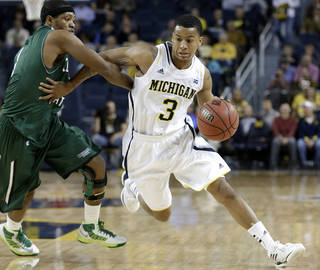 FILE - In this Nov. 13, 2012 file photo Michigan guard Trey Burke (3) drives around Cleveland State guard Sebastian Douglas (1) during the first half of their NCAA college basketball game in the second-round of the NIT Season Tip-Off tournament at Crisler Arena in Ann Arbor, Mich. Burke was selected to the AP All-America team Monday, April 1, 2013. (AP Photo/Paul Sancya, File) Paul Sancya