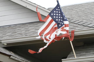 WESTMOOR HOUSING ADDITION / TORNADO DAMAGE / TORNADO AFTERMATH / CLEANUP: A tattered American flag, still attached to a damaged home in the Westmoor neighborhood in southwest Oklahoma City, blows in the wind Thursday, May 30, 2013. Photo by Aliki Dyer, The Oklahoman Aliki Dyer - The Oklahoman