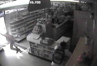 In this image from a 2009 surveillance recording, robber Jevontai Ingram flees out the door of the Reliable Discount Pharmacy in south Oklahoma City while a scond robber, Antwun Parker, is shot as he pulls on a mask.