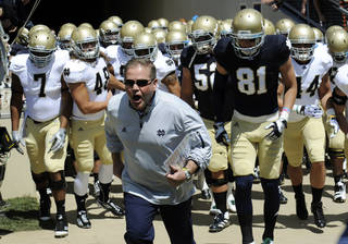 In this April 21, 2012, file photo, Notre Dame coach Brian Kelly leads his team onto the field for their spring NCAA college football game in South Bend, Ind. Kelly, in his third-year as head coach, has the unbeaten Fighting Irish in the national championship discussion with their best start in a decade at 7-0 and a big game Saturday at eighth-ranked Oklahoma. (AP Photo/Joe Raymond, File)