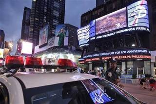 """A police officer stands guard in New York's Times Square as the ABC news ticker displays news of an al-Qaida terror threat, Friday, Sept. 9, 2011. Just days before the 10th anniversary of the Sept. 11 attacks, U.S. counterterrorism officials are chasing a credible but unconfirmed al-Qaida threat to use a car bomb on bridges or tunnels in New York City or Washington. It is the first """"active plot"""" timed to coincide with the somber commemoration of the terror group's 9/11 attacks a decade ago that killed nearly 3,000 people. (AP Photo/Mary Altaffer)"""