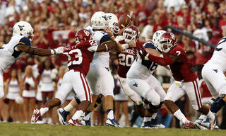 Oklahoma's Kass Everett (23) tips the hand of Paul Millard (14) for a fumble during a college football game between the University of Oklahoma Sooners (OU) and the West Virginia University Mountaineers at Gaylord Family-Oklahoma Memorial Stadium in Norman, Okla., on Saturday, Sept. 7, 2013. Photo by Steve Sisney, The Oklahoman