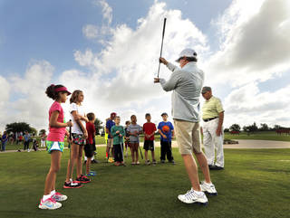 Assistant golf professional Bobby Florer teaches putting techniques to young participants in a free junior golf clinic at Westwood Golf Course in Norman. PHOTO BY STEVE SISNEY, THE OKLAHOMAN STEVE SISNEY