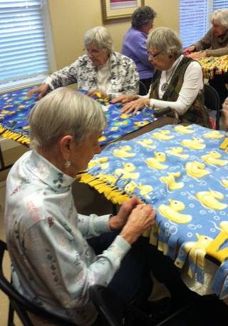 Lee Disbrow, foreground, works on fleece blankets with Darlene Schrader, left, and Louise Haaland. PHOTO PROVIDED BY CAROL HARTZOG COMMUNICATIONS